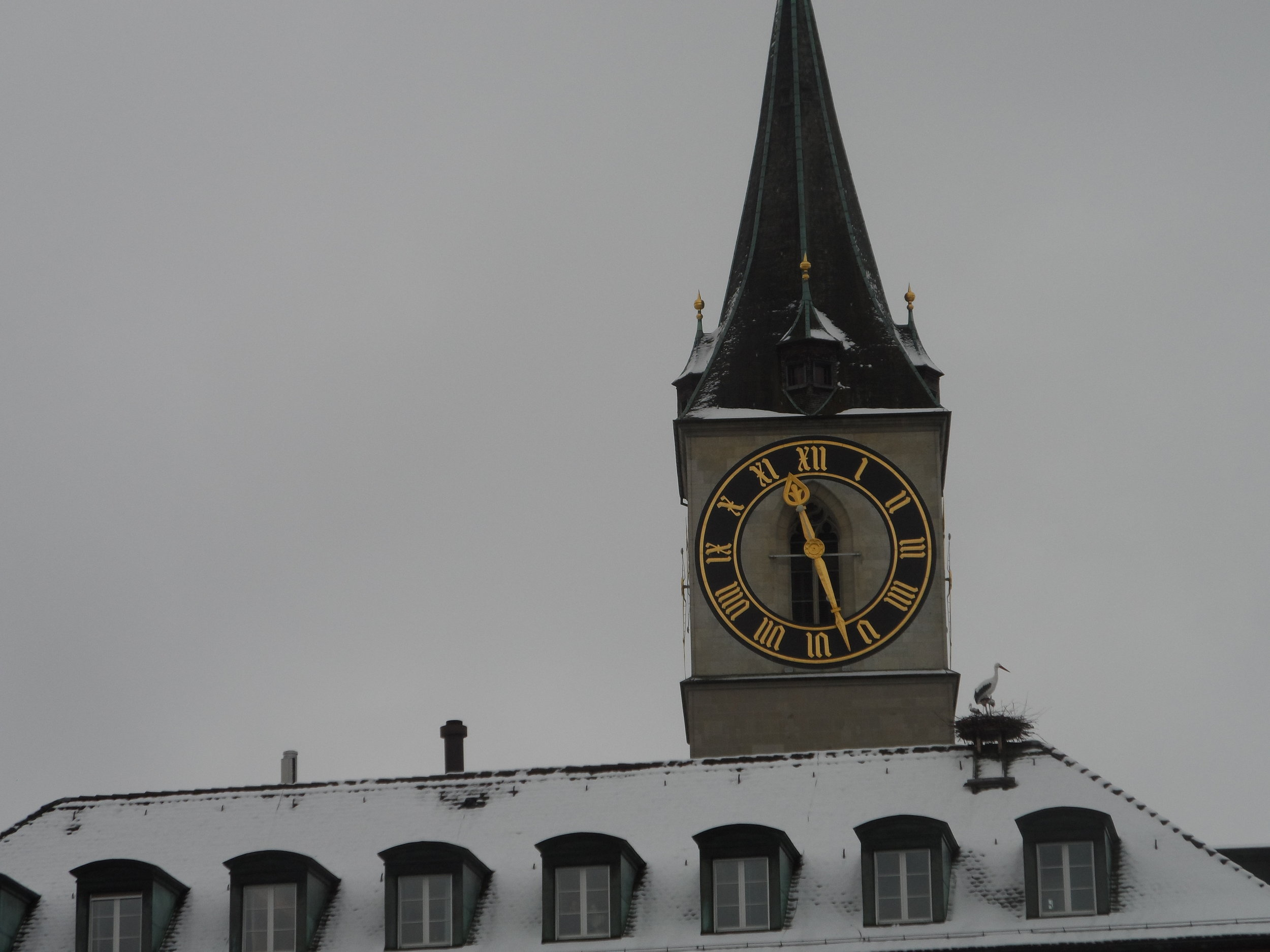 A Closer View of the Large Clock on the tower of the Peterskirche—note the stork's nest!