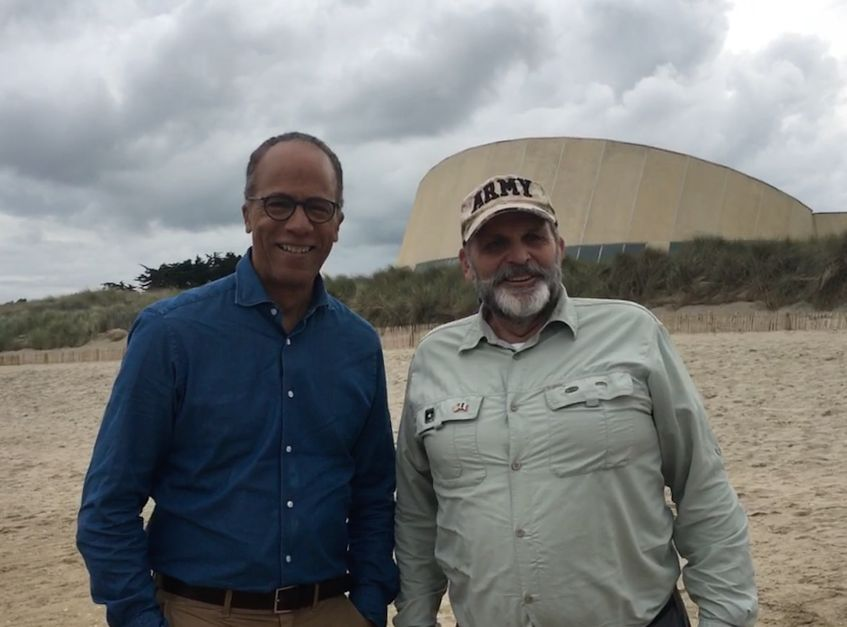 Lester Holt and Hank Utah Beach 2019—the Utah Beach Museum is in the bacjground