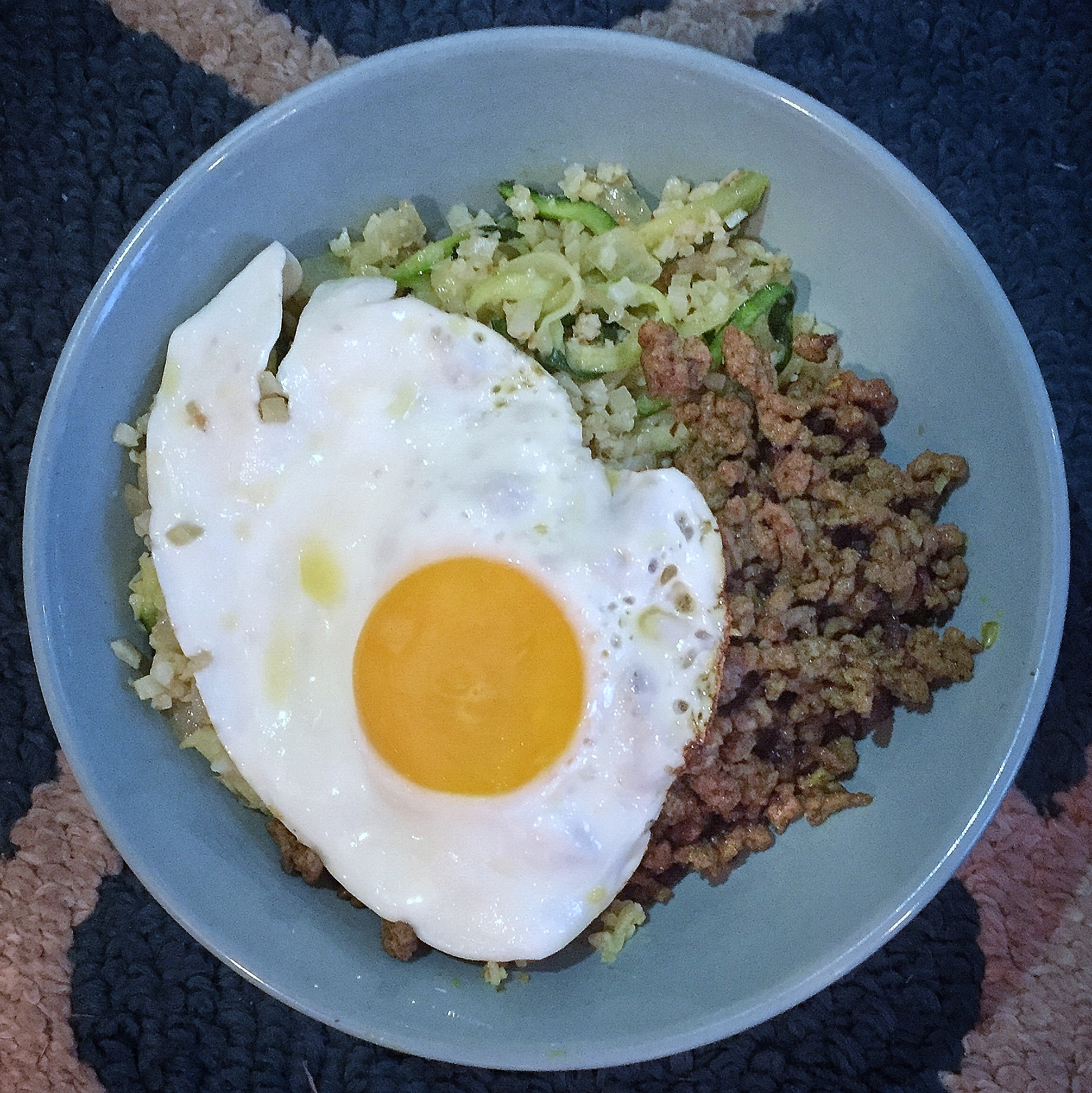 Ground beef seasoned with curry and mixed with zoodles (zucchini noodles), onions, cauliflower rice, and topped with a fried egg!