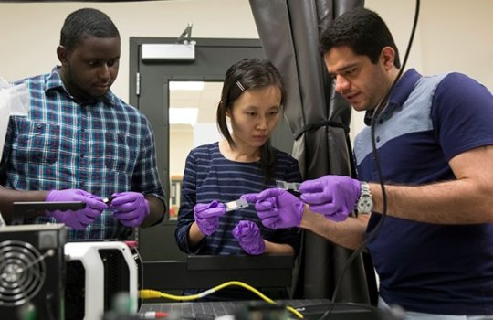 Assistant professor Congrui Jin (centre) with two Binghamton University graduate students from the Mechanical Engineering Department. Image Credit: Jonathan Cohen.