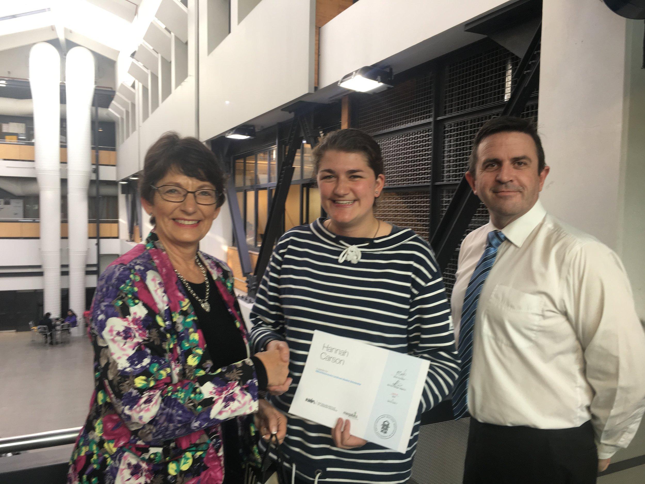 Marilyn Best from Megabits and Michael Wright (NZILA Wellington Branch Secretary)present Hannah Carson with her award.
