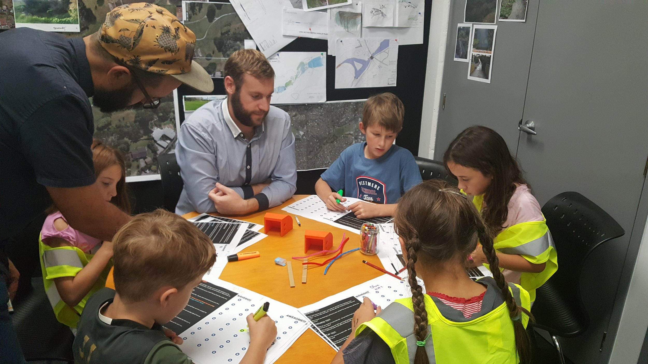 Damian Powley (left) working on design with a group of children.