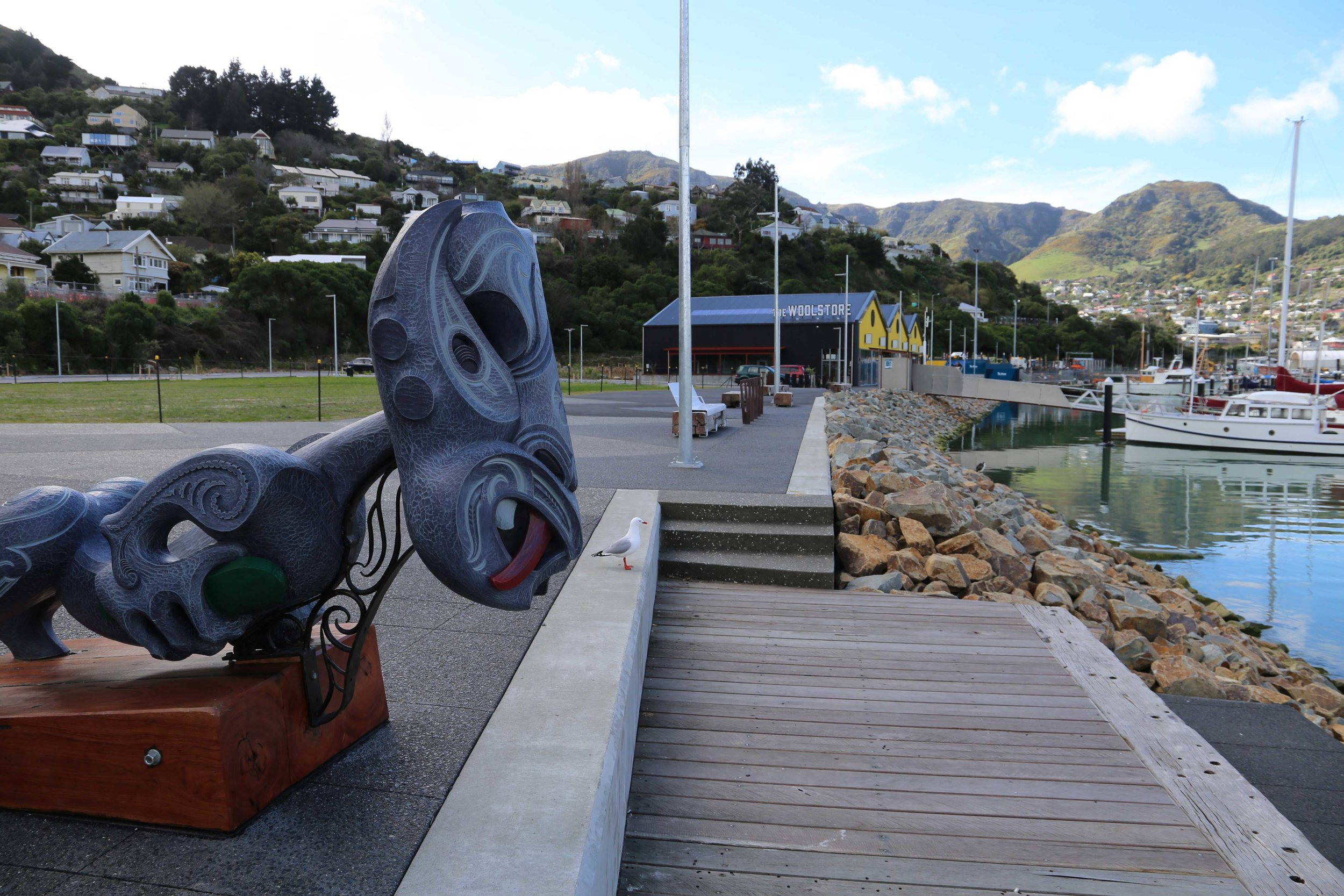 The tauihu sculpture created by Whakaraupo Carving overlooks the terrace of milled reclaimed wharf piles and out toward Lyttelton Harbour.