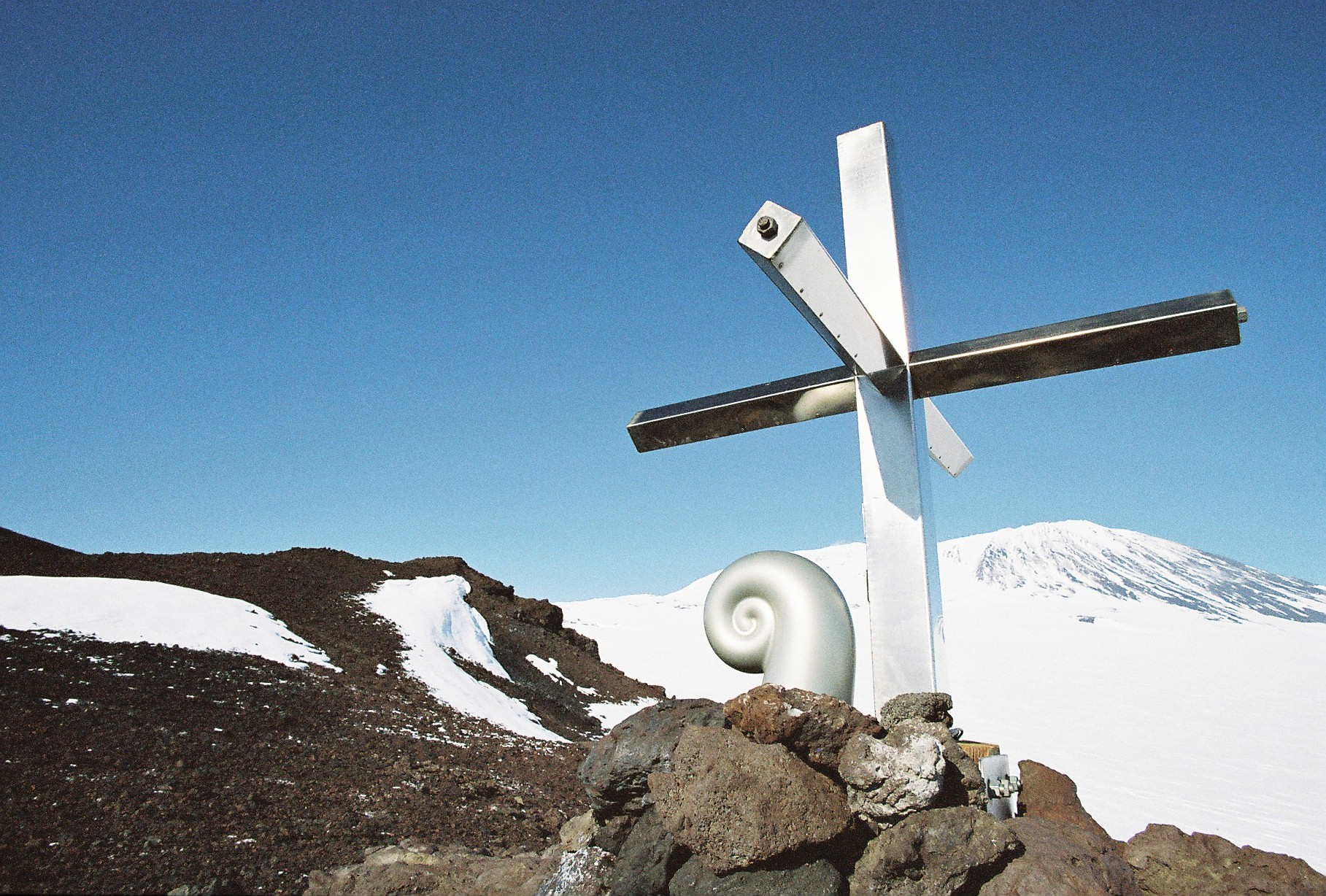Koru capsule and cross on Mt Erebus. The cross is located approximately 3 km south-east of the 1979 crash site. This stainless steel cross was erected in 1987 to replace the original wooden one, which had eroded. The Koru was created by Christchurch sculptor, Phil Price. Photo credit: Daniel O'Sullivan, 2009-10, Antarctica New Zealand Pictorial Collection.