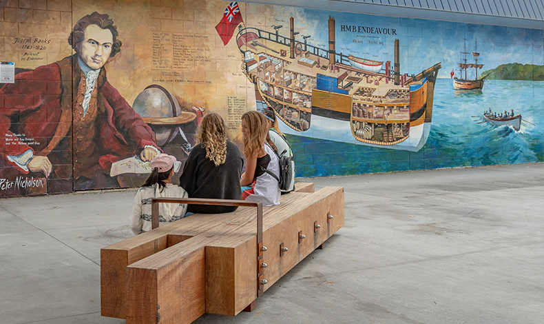 Whitianga Art group member, Peter Nicholson, created this mural on the wall of the Mainly Casual building immediately next to the new Whitianga town plaza in Albert Street. It depicts the Endeavour ship and botanist Joseph Banks (a member of the Endeavour's crew).