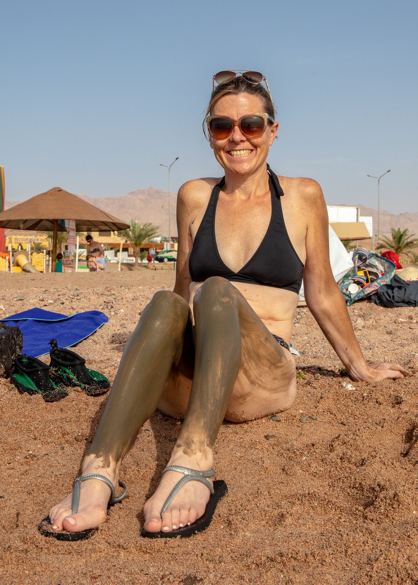 Veronica covering up with Dead Sea mud providing by the lovely English/Kiwi family we met