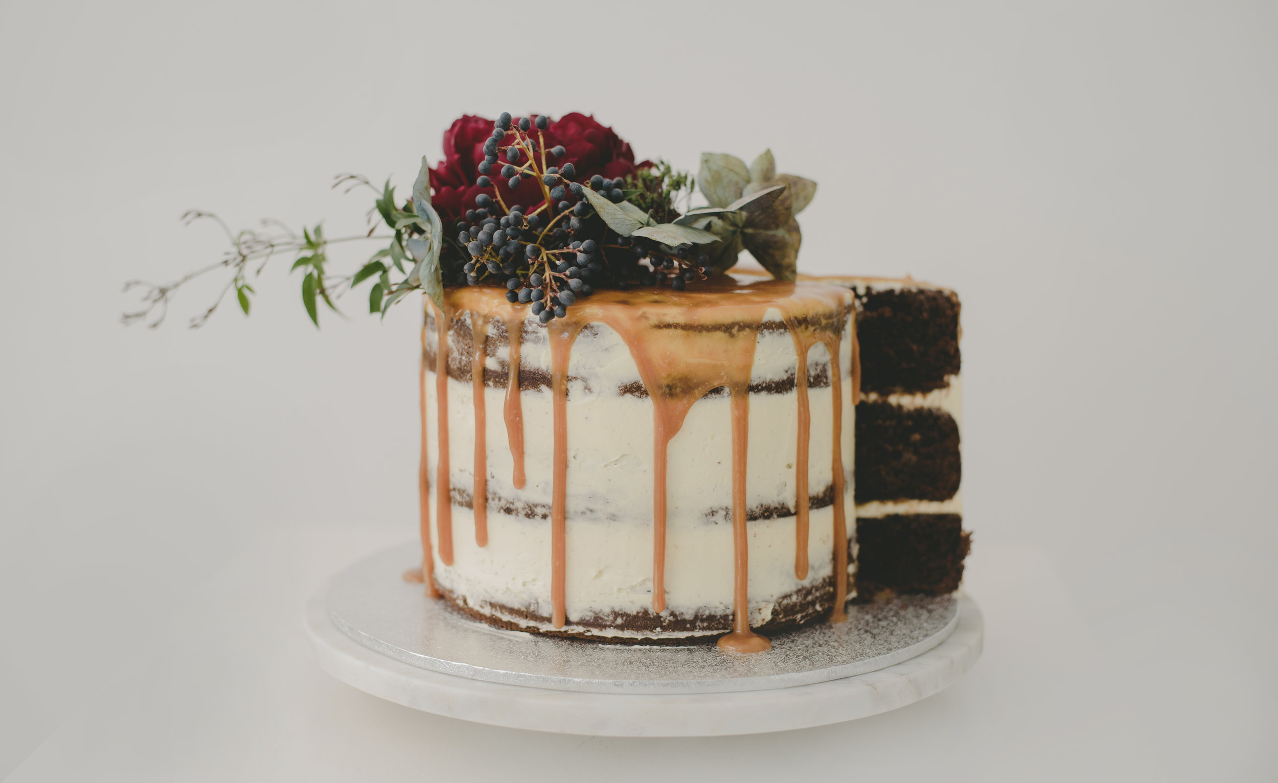 Chocolate layer cake filled with salted caramel finished with a salted caramel drip and fresh blooms courtesy of  Fleur & Hunt  x