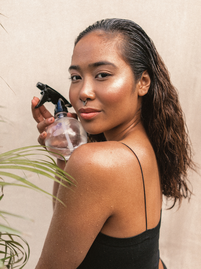 ethnic minority Filipino woman with coconut oil in her hair and wet skin holding a diy moisturiser hair spray bottle