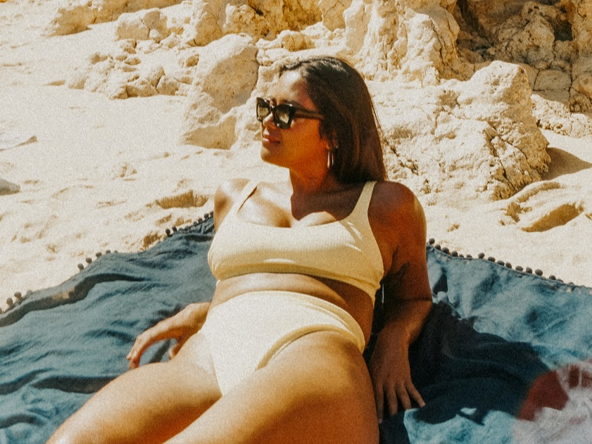 a curvy woman wearing sunglasses and a yellow bikini sitting up on a beach blanket with sand and rocks in the background