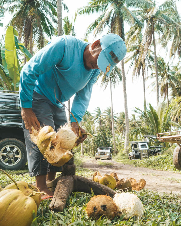 a farmer wearing blue top and cap standing in front of a car using equipment to remove a coconut from its shell
