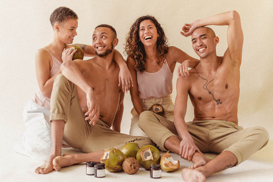 four people sat together on the ground smiling with coconuts and three jars of Virginutty coconut oil placed in front of them