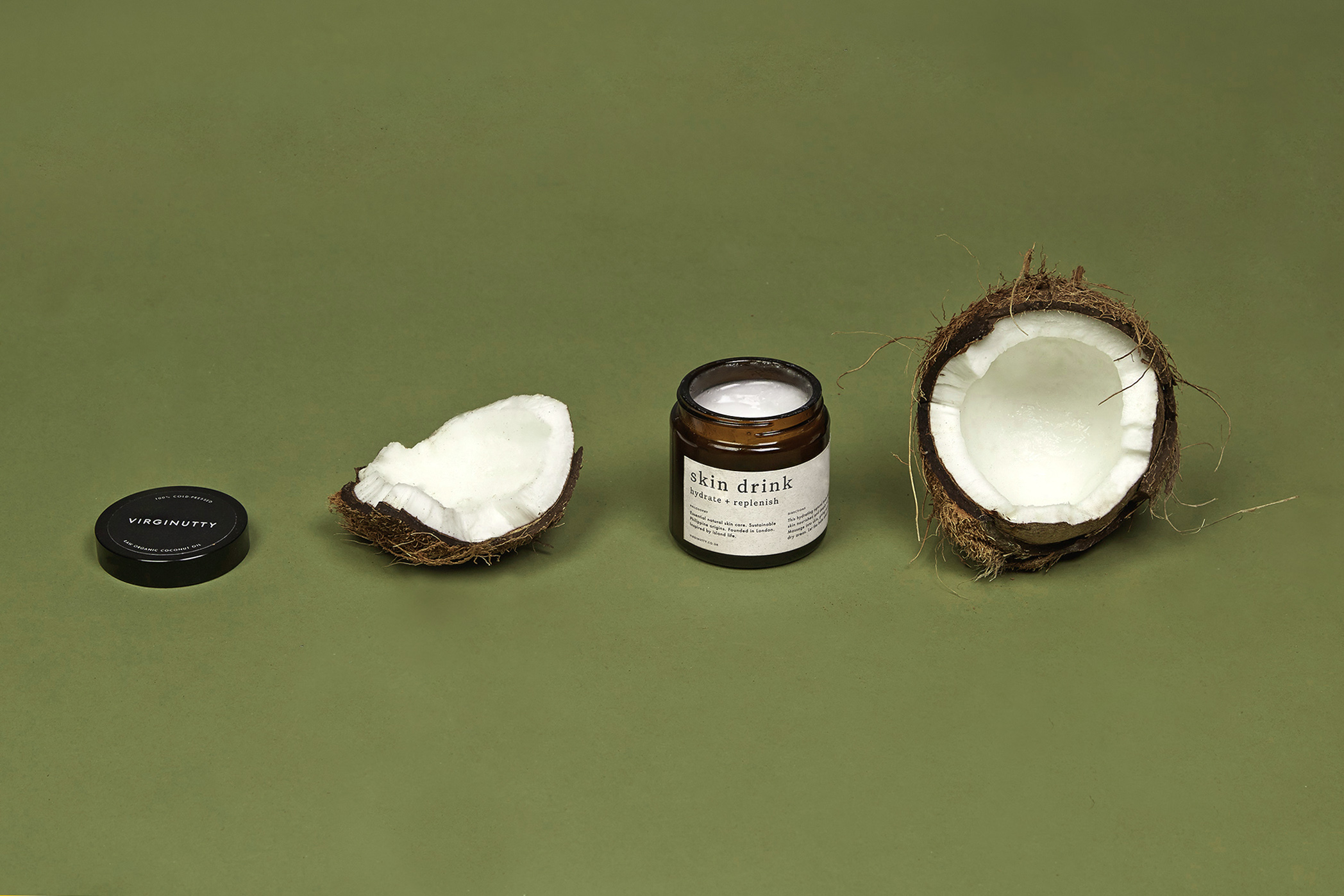 four items spaced equally apart on a green surface: a coconut split into half and Virginutty's Skin Drink with the lid taken off and placed separately
