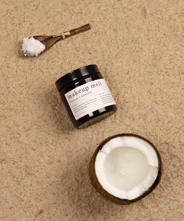 brown wooden spoon with raw coconut oil on it laid next to a jar of Virginutty's Makeup Melt cleanser and a half a coconut