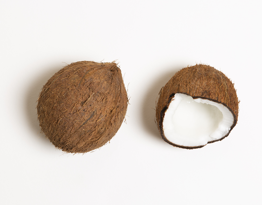 a whole brown coconut and half a coconut placed together on a white surface