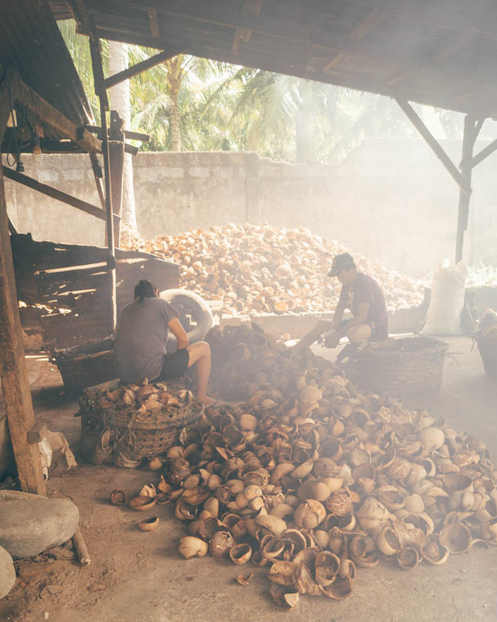 two workers sat in a dark hazy roofed outdoor workspace amongst dozens of removed coconut shells on the floor