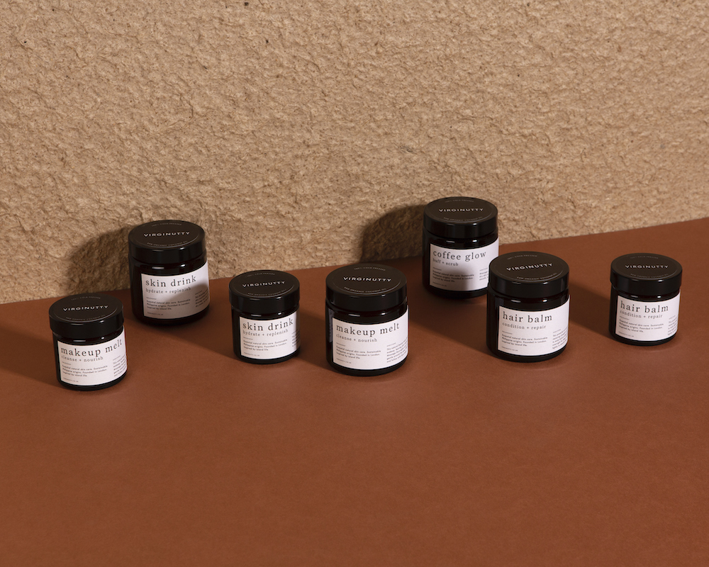 several jars of Virginutty's Skin Drink, Makeup Melt and Hair Balm all placed next to each other on against a two-tone peach and terracotta background