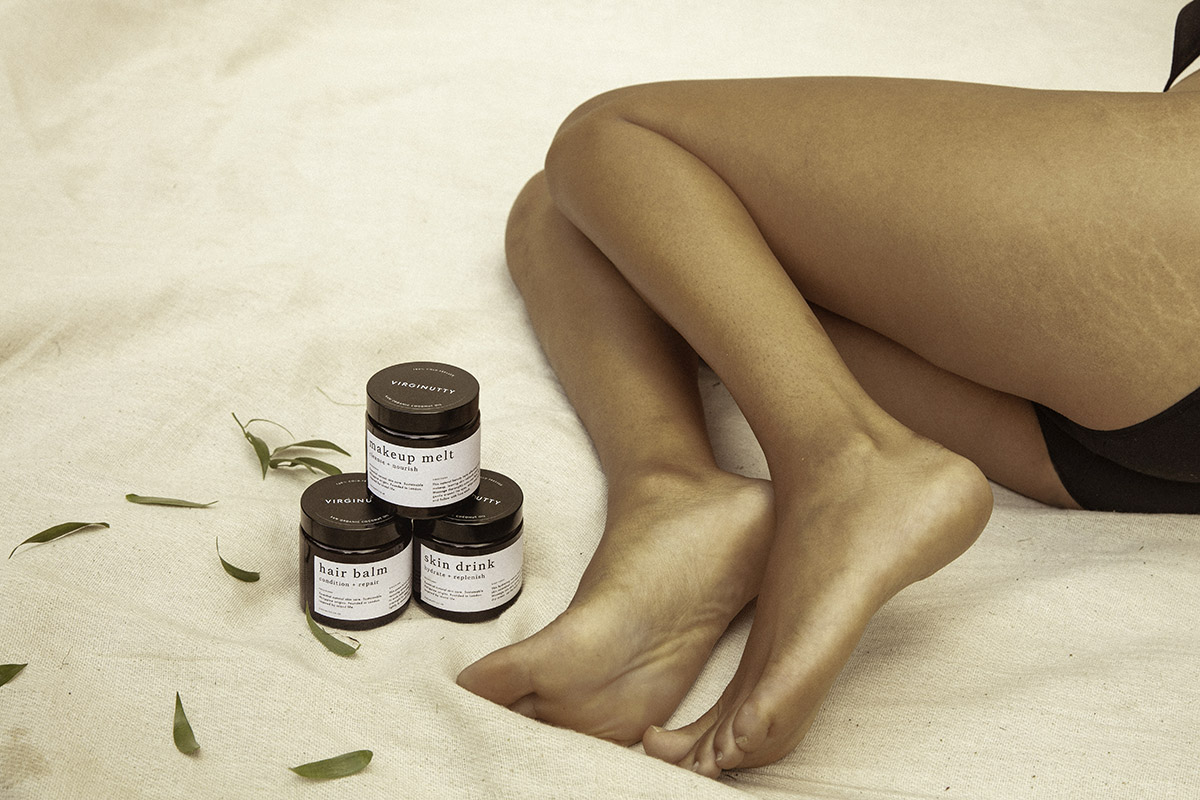 three jars of Virginutty's Hair Balm, Makeup Melt and Skin Drink placed together next to a woman sat with her tanned legs folded