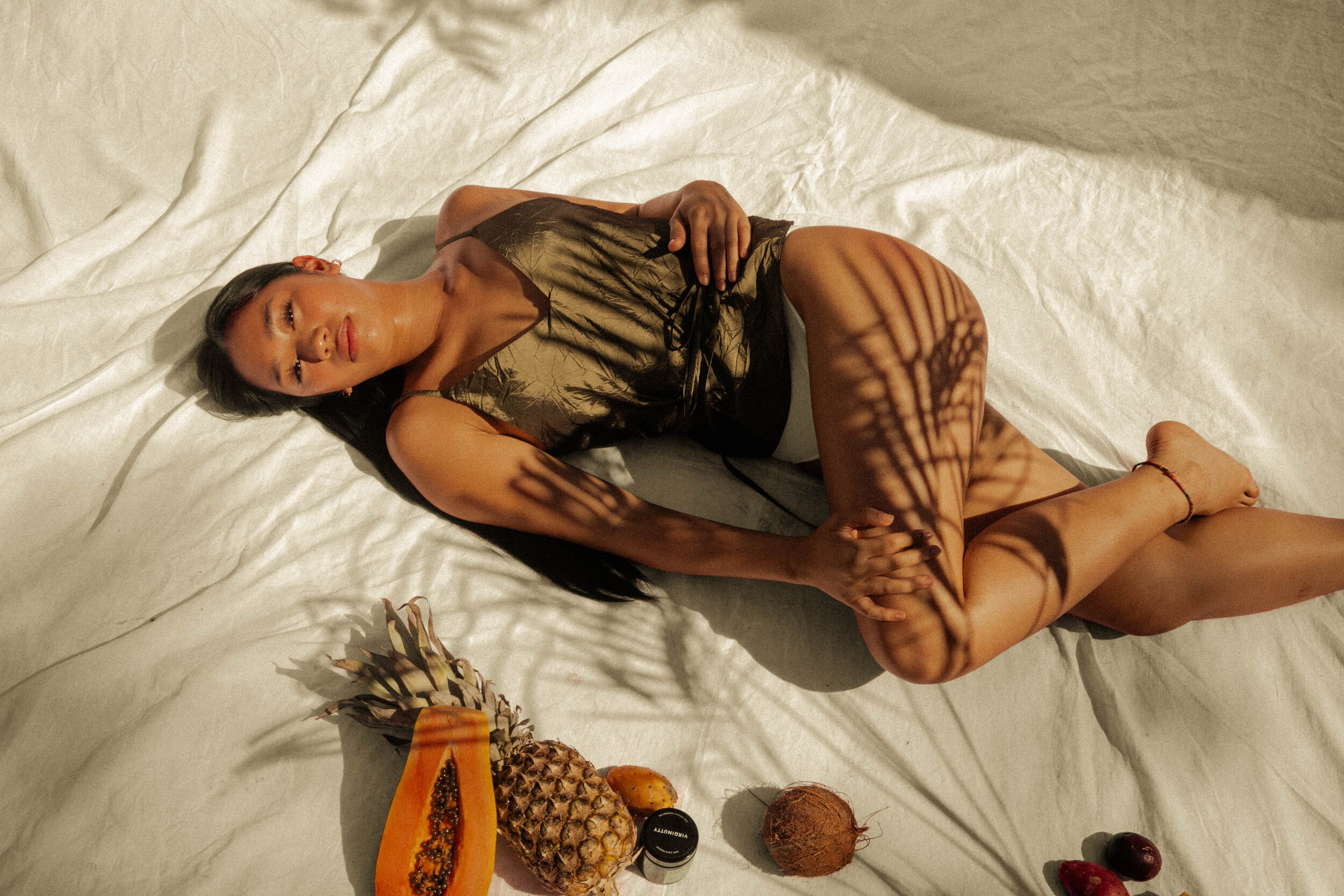 a woman lying down on a white sheet next to a pineapple, papaya, tropical fruits and Virginutty topical cbd coconut oil moisturiser