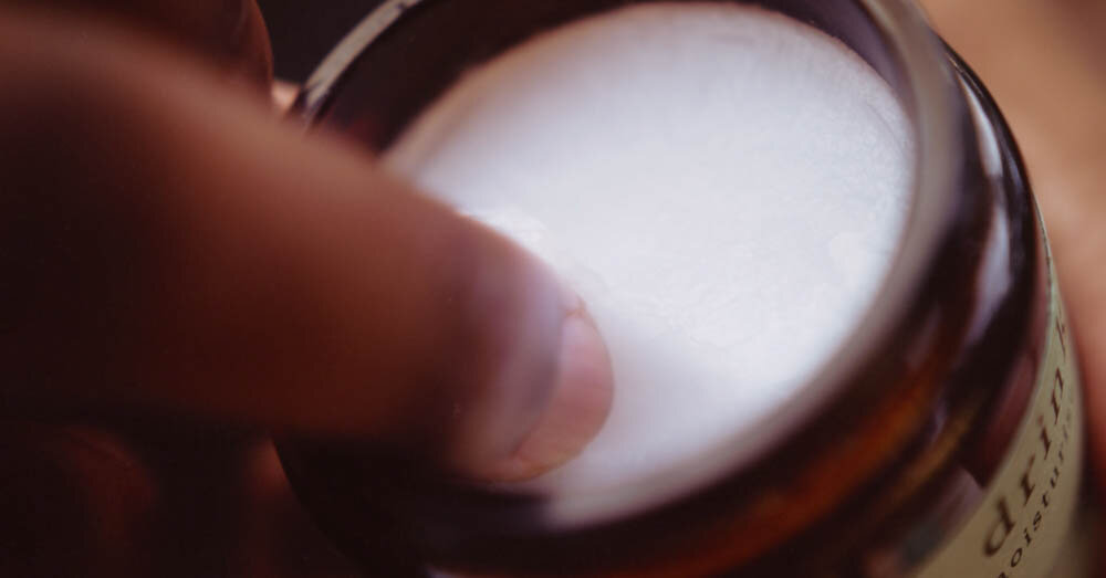 a finger scooping CBD coconut oil out of a jar