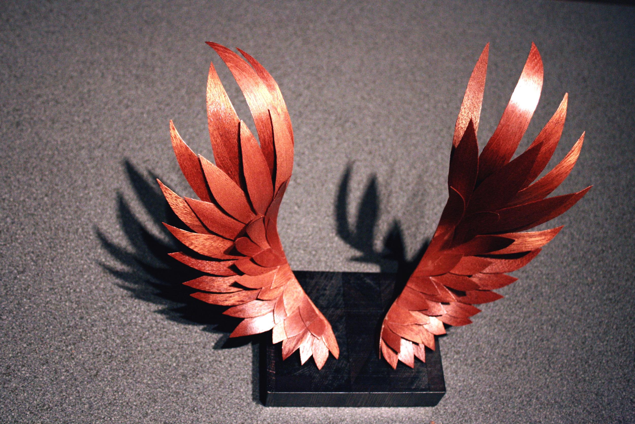 VÆRA    Náttúrulegir, lakkaðir  Fáanlegir í Hnotu, mahóní og Fuglsauga (Birds eye maple)  Hver vængur er um 25-28 cm langur. Vængirnir standa út af platta og vísa upp.  Hvert par tekur um 8 klst. í vinnslu.  Vænghaf um 25-30 cm.  Koma í svörtum og náttúrulegum lit og lakkaðir.  29.000 kr. / 240 € / 290 USD