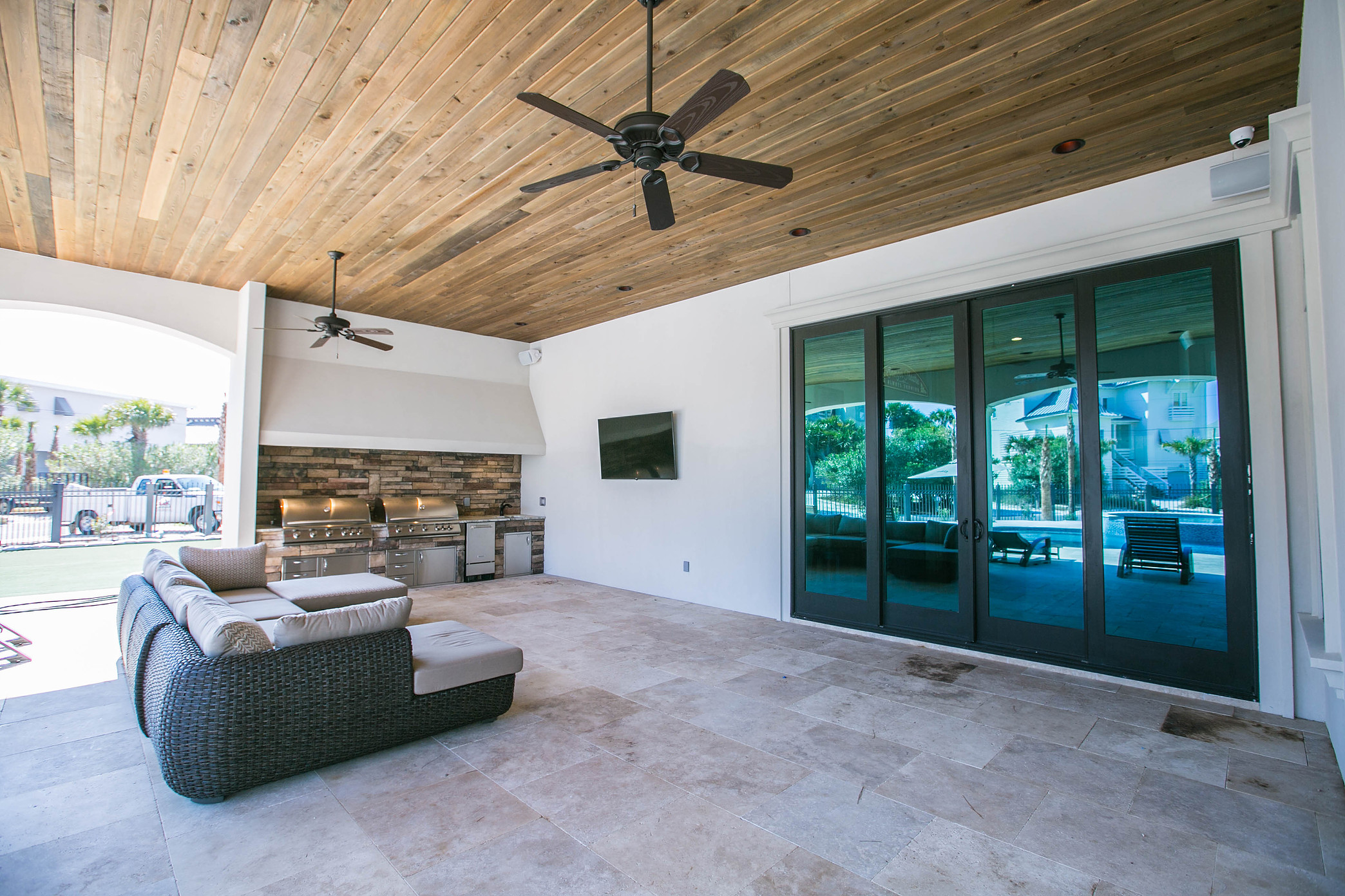 Custom Home with wood planked ceiling in outdoor living area