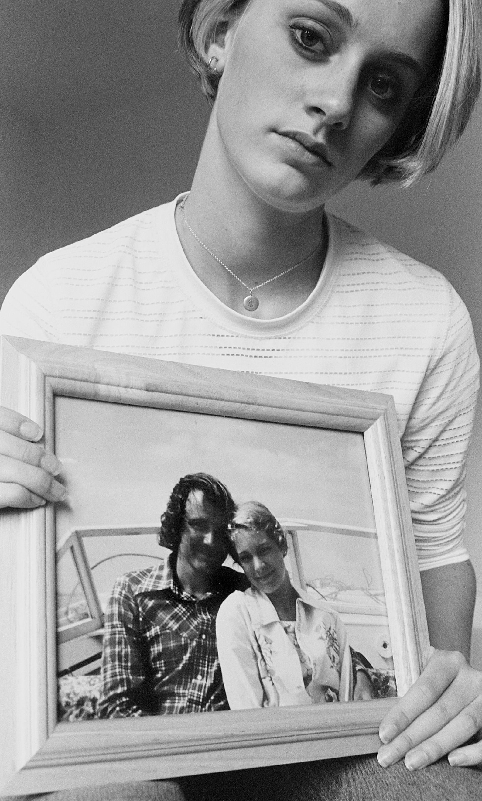 Crystal, holding photo of the honeymoon after the divorce but before the death, 2019/2001