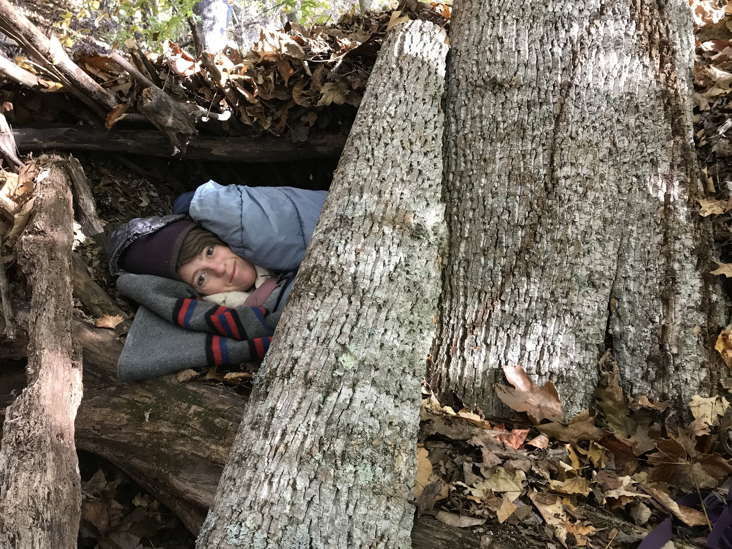 woman sleeping in natural shelter