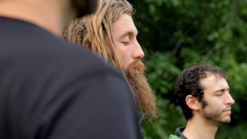 man with beard meditating