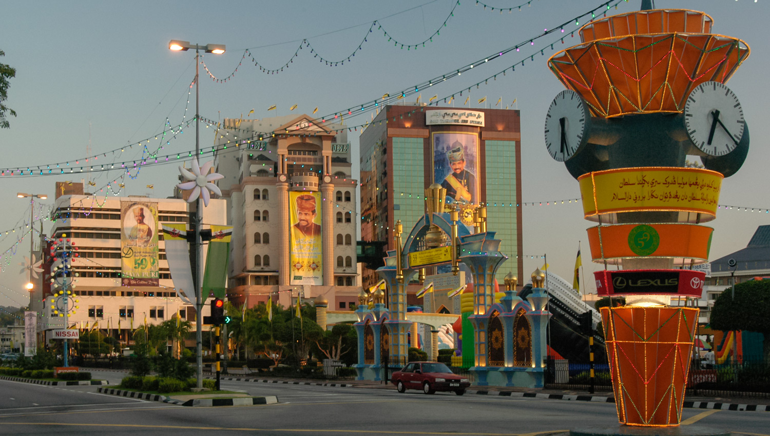 Buildings in downtown BSB displaying posters of the ruling sultan. Image: © David Astley