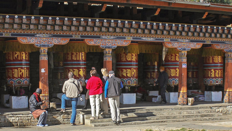 Visitors inspecting prayer wheels in Thimphu. Image:  © Alan Williams