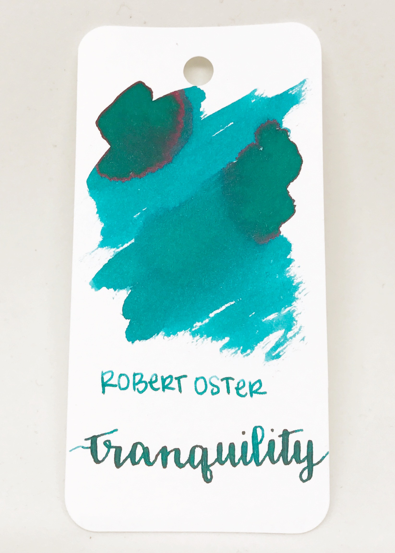 The color: - Tranquility is an amazing teal, with a pink sheen. On some papers it looks more blue, and others it looks more green. Seasonally, I would use this in the winter. On the swab, it looks a lot brighter than it does in everyday writing.