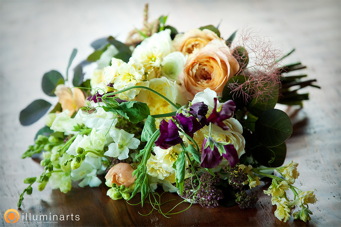 Wedding bouquet with sweet peas and ranunculus, purple peach yellow and white