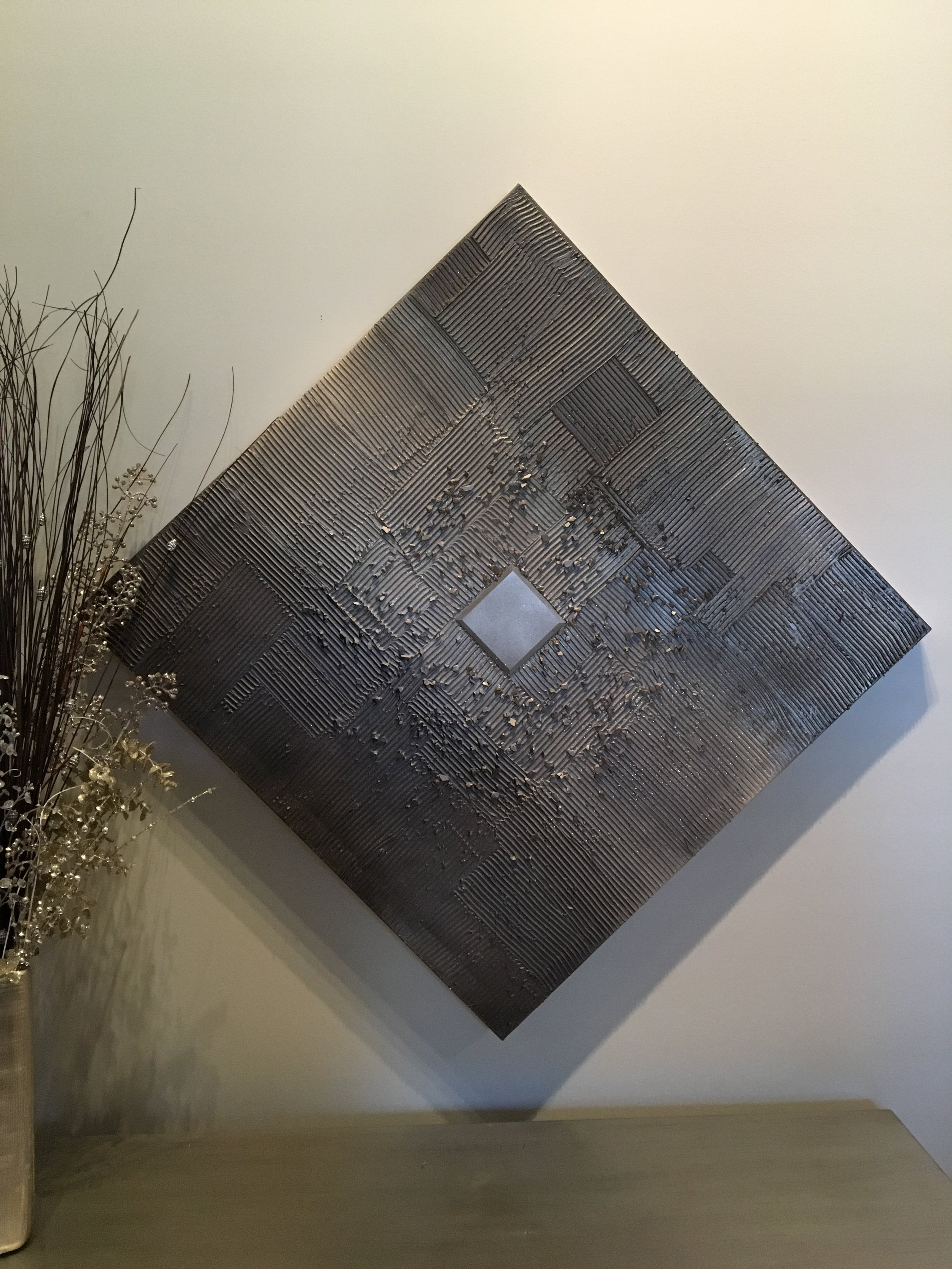 'Bronze Buckle' is a 36x36 with copper, graphite and bronze tones with lots of stones surrounding the center.