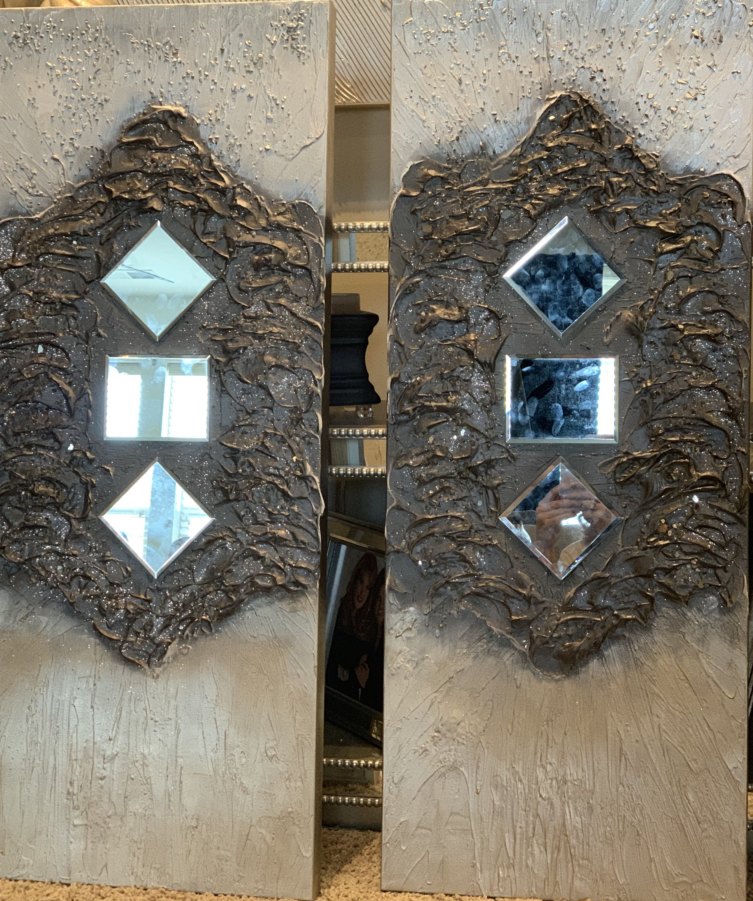 'Charisma' is shown as a pair of 16x40 with layers of texture. the beveled mirrors are on a backdrop of oil rubbed bronze with a touch of sparkle. The top texture is silver tones and the bottom is champagne.