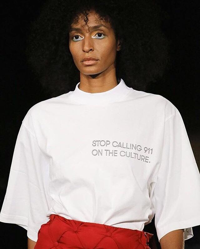This one goes out to all the h8ers 🤬 . . Image description: photo of a womxn walking in the #pyermoss show wearing a shirt that says, 'stop calling 911 on the culture' . . 📸✨ @r29unbothered