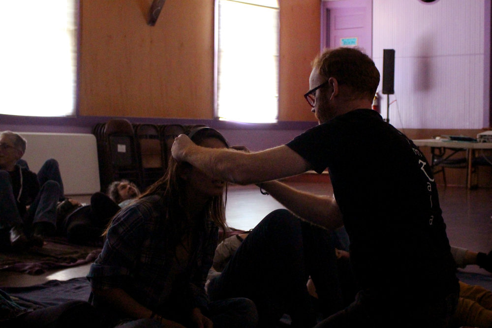 Mentor Jermey McKane fits a neuro feedback machine to a fellows head