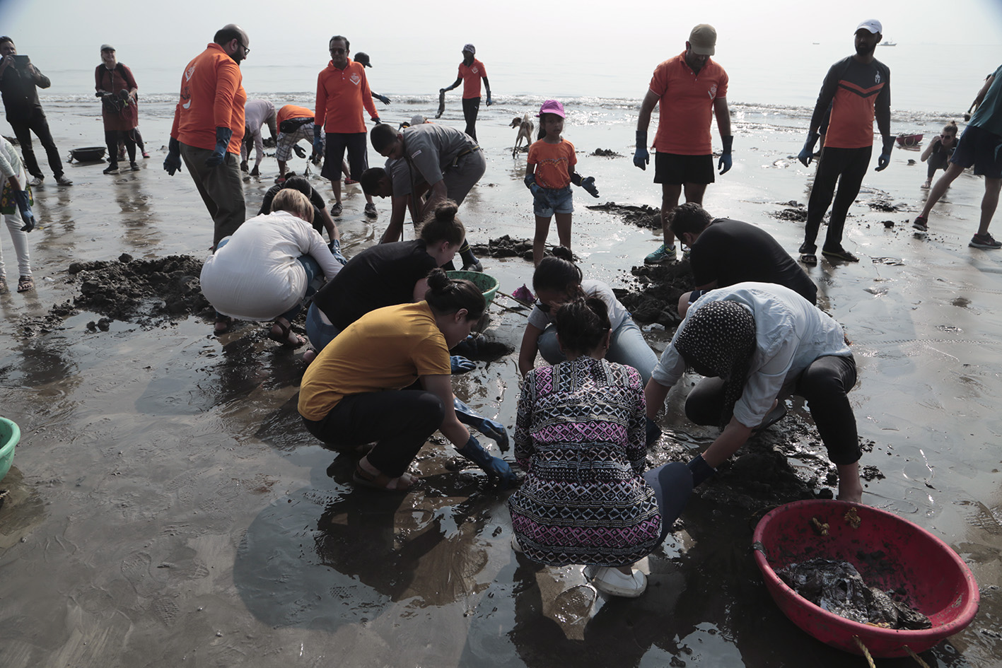 Pulling out plastic bags from under the sand on Versova Beach