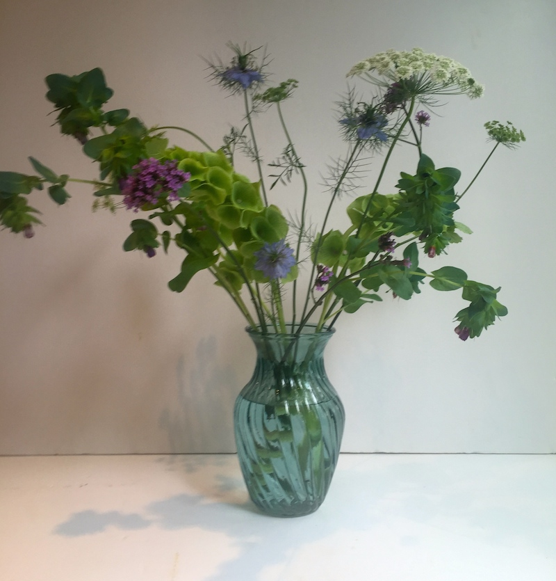 Step 2 - Start building your arrangement by adding your filler flowers - so things like Ammi, Solidago are great fillers. Here we are using Ammi and some Nigella....