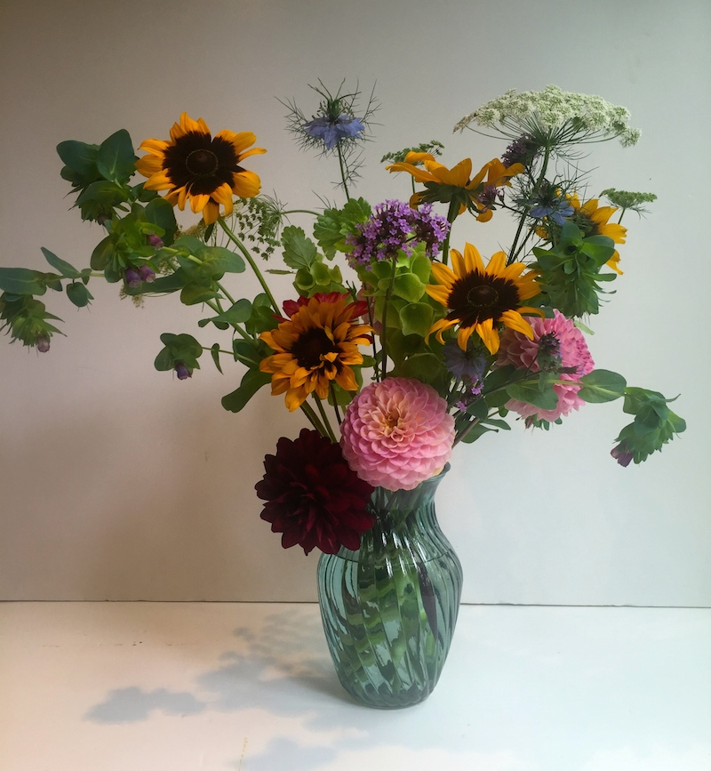 Step3 - Now for the fun bit. Once you have your framework made up of secondary/filler flowers and foliage (if you don't have any foliage go cut some from the garden!) start to add you focal flowers. These are your bigger 'wow' flowers. Here we are using Rudbeckia and Dahlias...try to work with odd numbers so 3's or 5's as it will be more pleasing to the eye.