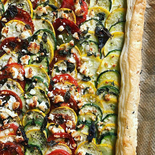 Heirloom tomato and courgette tart with fresh herbs and feta in just 5 steps... — — 1. Roll out a sheet of puff pasty, score a border along the sides with a knife and using a fork, poke the middle several times (this will prevent excess puffing)  2. Layer thinly sliced veggies; I used tomatoes and courgettes. Beets are also pretty! 3. Fold the sides of the pastry over to form a crust and lightly brush everything (veggies & crust) with olive oil. Add a good grind of salt & pepper.  4. Tear up mixed herbs (I used lemon basil, oregano & thyme) and scatter on top, crumble  some good feta and scatter that too.  5. Bake in the oven for about 15-20 mins or until the crust and feta appear  golden brown.  ENJOY! — — #feta #heirloomtomatoes #courgettes #courgettetart #puffpastry #quickrecipes #puffpastrytart #savourytart #zucchini #simplerecipes #vegetarianrecipes #freshherbs #fetacheese #goldenpastry #quicktart #easyrecipes #basil #oregano #thyme #leeds #chapelallerton