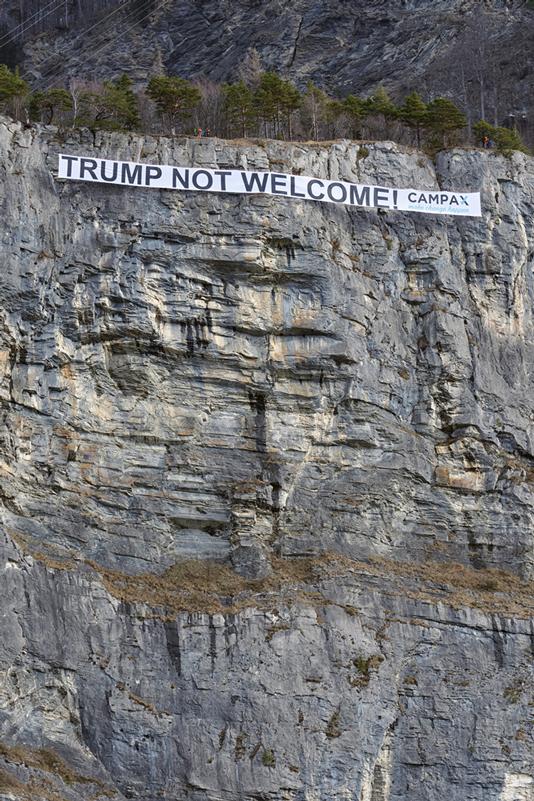 """Campax protestiert in Sargans gegen Trump-Besuch.   Donald Trump will noch im Januar zum WEF in Davos reisen und dort seine Politik """"America First"""" erklären und verteidigen. Müsste es nicht """"The World First"""" heissen? Eine Politik, die nur auf Eigennutz, Wachstum und Machtzuwachs gründet, führt weder zu Wohlstand noch zu Frieden. Die Gruppe Campax hat am Donnerstagmorgen mit einer ungewöhnlichen Aktion gegen die Teilnahme von US-Präsident Donald Trump am WEF in Davos protestiert. Kletterinnen und Kletterer hängten ein 60 Meter langes Anti-Trump-Transparent in eine Felswand bei Sargans SG  Bild: Antonino Panté / Keystone / AP / sda"""