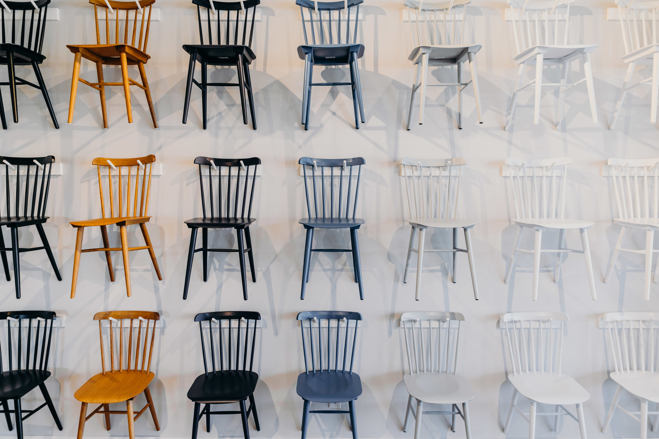 Retail display of multicolored dining chairs hanging on shop wall