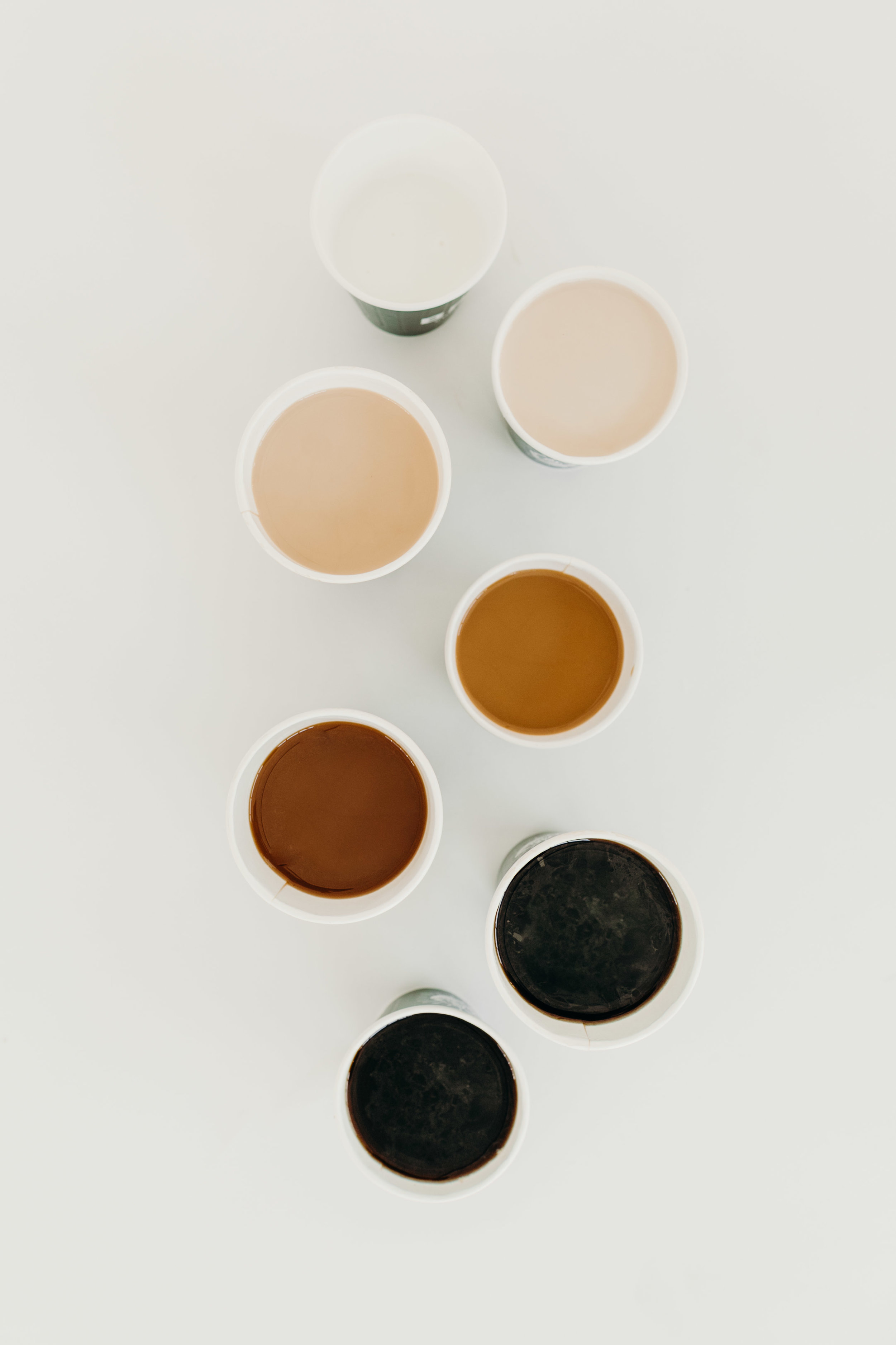 Overhead view of various beverages in paper cups from Brash Coffee
