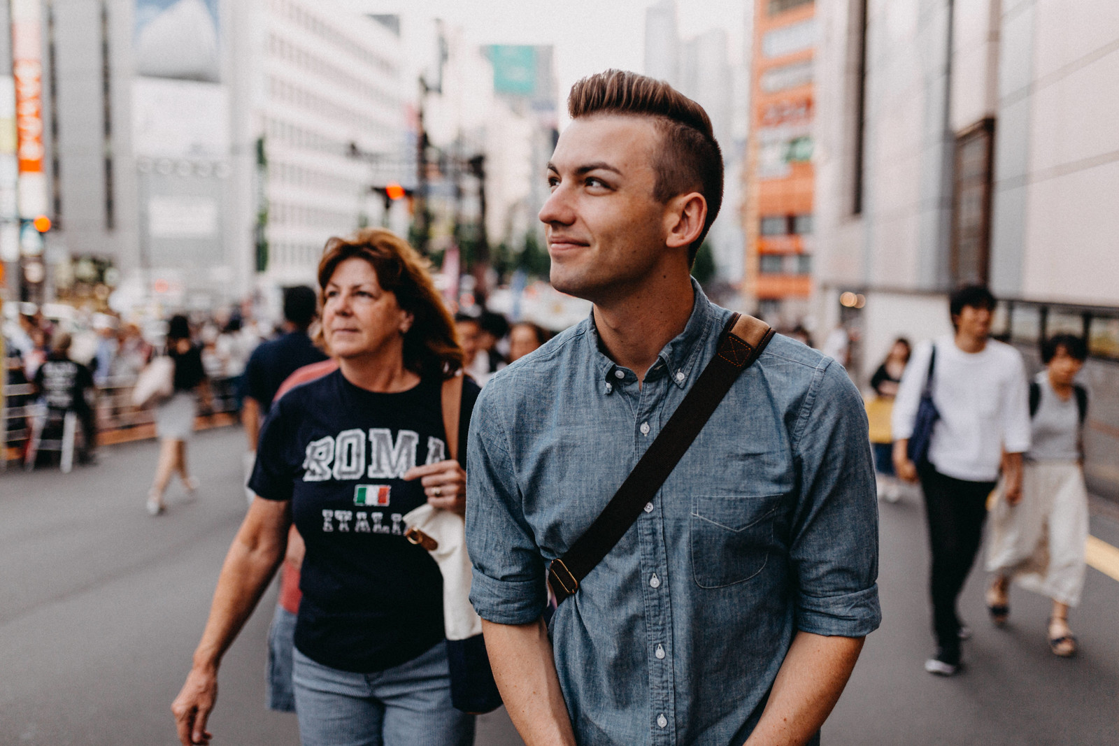 Gay backpacker and mom walking through Shinjuku on first visit to Tokyo Japan