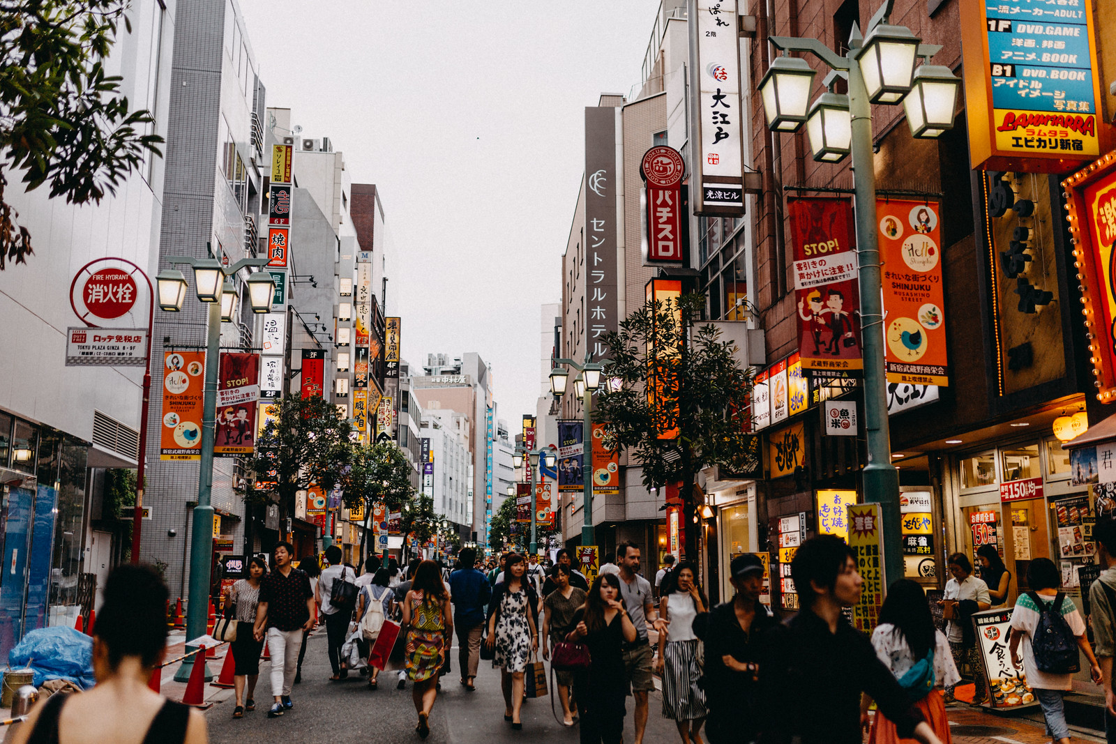 Lit up streets full of people at dusk in Shinjuku Tokyo Japan with restaurants bars and arcades