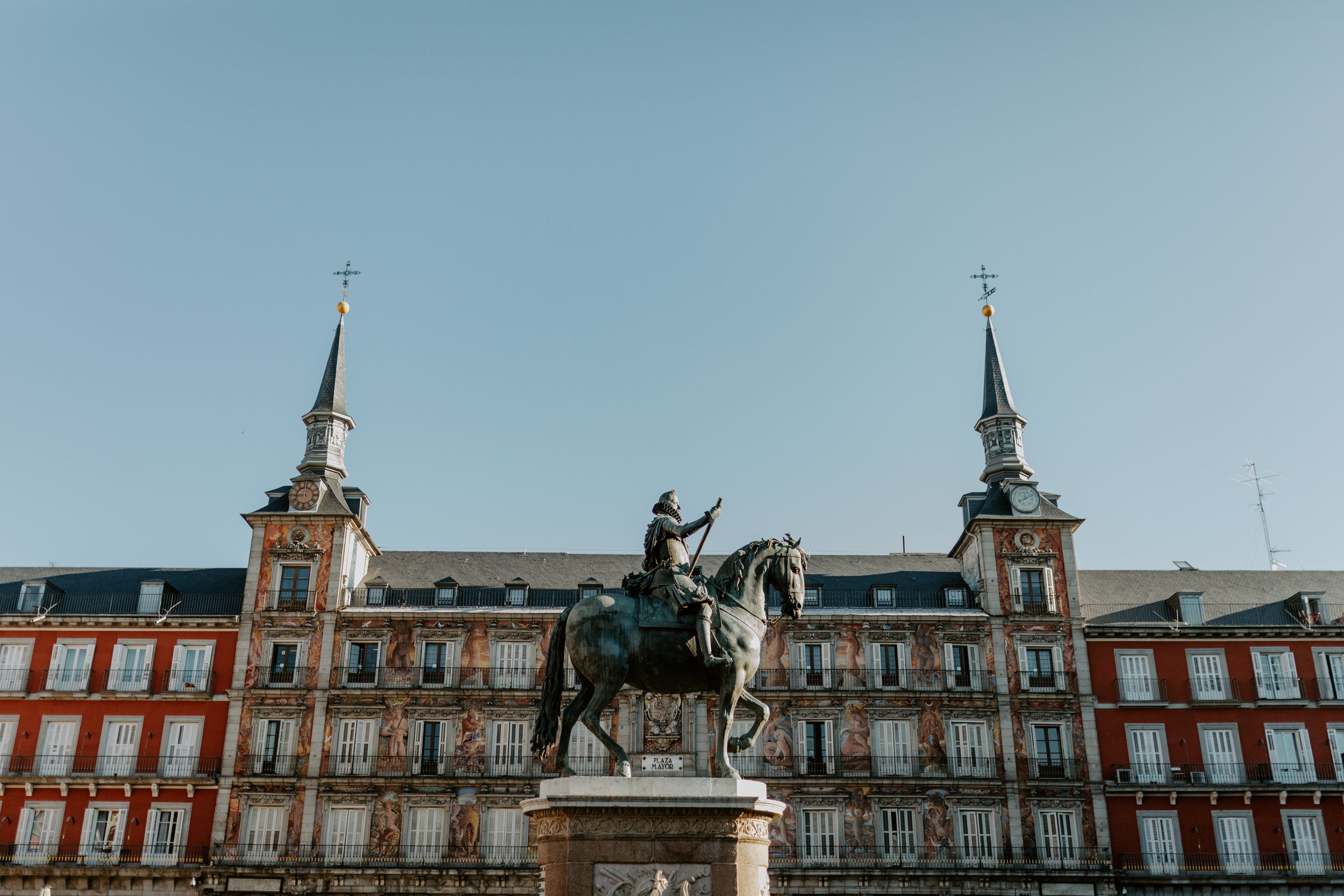 King Philips III's bronze statue is set in the center of Plaza Mayor. Surrounding, a lively square of vendors, tourists, locals passing through and waiters tending to their tables.