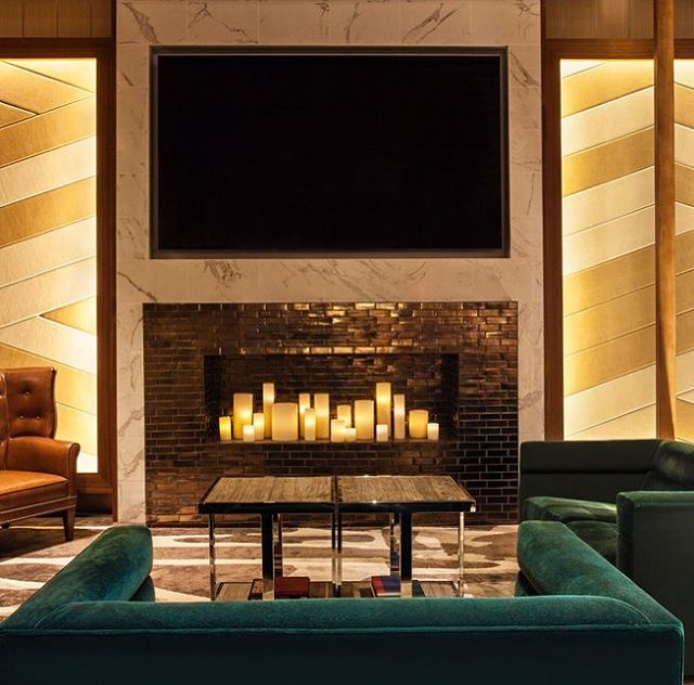 The up-lit wood screens create a sense of drama, while a candlelit fireplace adds the warmth and comfort of the residential hearth to the Westin Hotel Time Square lobby. The neutral color palette, with luxurious fabrics and pops of green, adds an understated elegance throughout the space and builds on Westin's nature connection. #ICRAVEdesigned #hoteldesign #interiors #westinhotel #timesquare