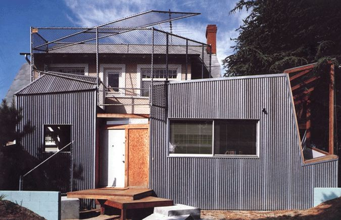 Gehry Residence in Santa Monica, 1978. One of the earliest examples of deconstructivism as can be seen in its angular forms, the reappropriation of commonplace materials like plywood, corrugated steel, and chain-link fence show a connection to postmodernism. Image Source:  ArchDaily