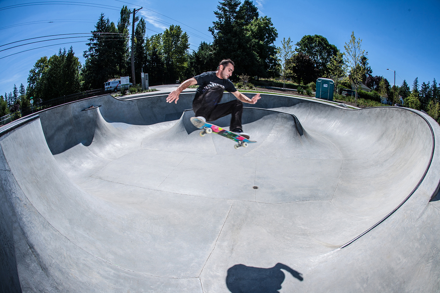 Professional skater Daniel Cardone ollies across two distant transitions at the Holly Farm Skate Spot.