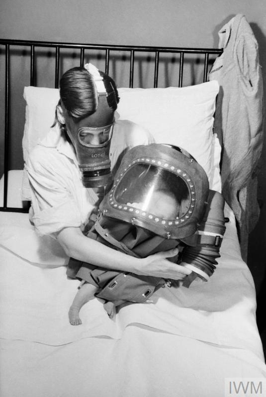 AIR RAID PRECAUTIONS ON THE BRITISH HOME FRONT: MOTHER AND BABY IN GAS MASKS, C 1941© IWM (D 3918)